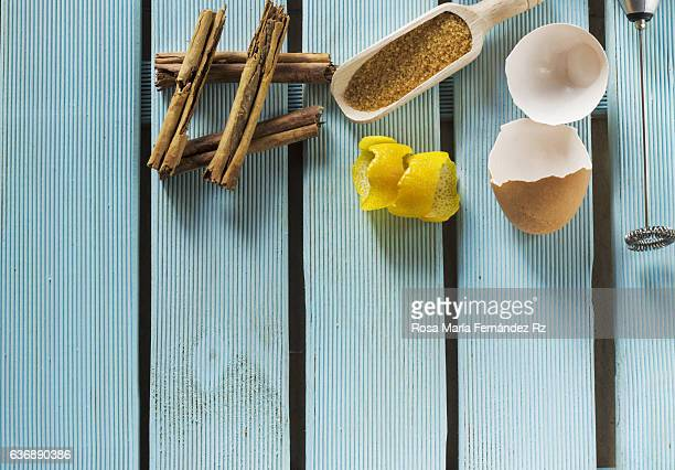 Overhead of custard in pot with cinnamon, lemon peel, bronw sugar cane,  beater and eggshell on blue wooden table. Subjects captured against soft window lighting. Copy space