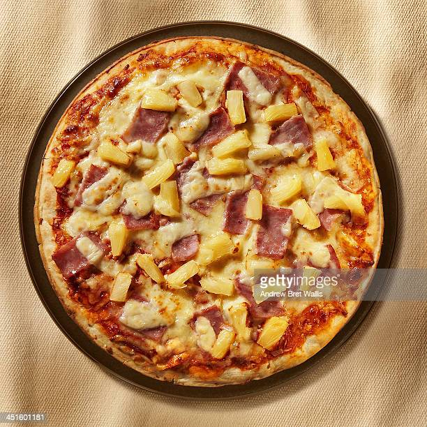 overhead of freshly baked ham and pineapple pizza - hawaiian pizza stock pictures, royalty-free photos & images