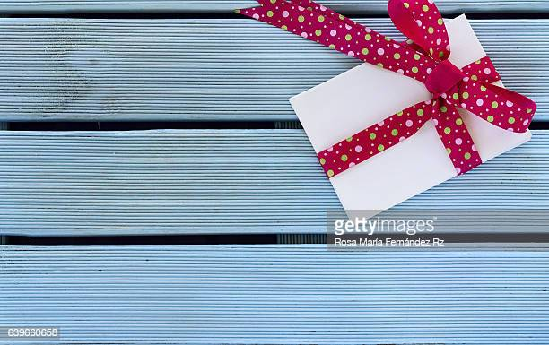 Overhead of handmade gift with vibrant bow tie on blue wooden background and copy space. Subjects captured against soft window lighting