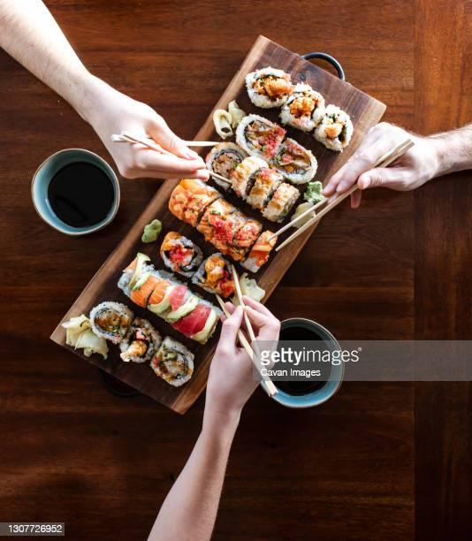 overhead of hands using chopsticks to pick up sushi rolls off platter. - prato de soja - fotografias e filmes do acervo
