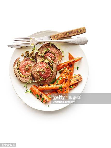 Overhead of herb-stuffed flank steak with carrots