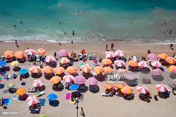 Overhead of people on beach with sun umbrellas