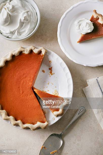 Overhead of sliced pumpkin pie with whipped cream
