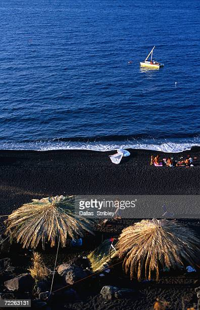 overhead of strolling and sunbaking on the black volcanic sands of piscita beach, piscita, italy - äolische inseln stock-fotos und bilder