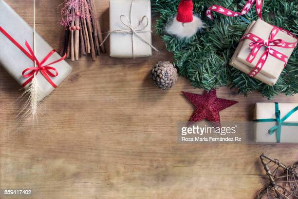 Overhead of wrapped christmas presents, fir tree branches, and christmas ornaments on wooden background. Copy space.