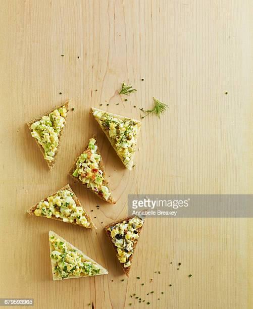 Overhead open faced egg salad sanwich on wood