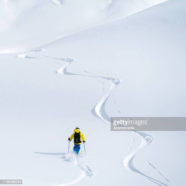 overhead perspective of a powder skier descending pristine slope - back country skiing stock pictures, royalty-free photos & images