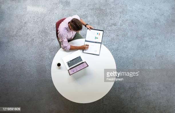 overhead foto van zakenman die bij een ronde lijst werkt - hoog standpunt stockfoto's en -beelden