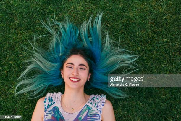 overhead portrait carefree young woman with blue hair laying in grass - untar fotografías e imágenes de stock