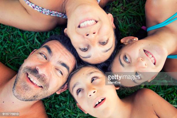 Overhead portrait of a happy family lying on the grass