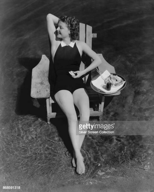 Overhead portrait of American actress Ann Sheridan as she sits on a chair in shallow water and eats a sandwich late 1930s This image has been...