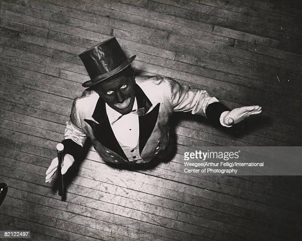 Overhead portrait of an unidentified man in costume in blackface a top hat twotone formal jacket waistcoat and gloves as he stands on a wooden floor...
