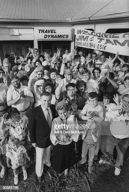 Overhead portrait of disgraced PTL evangelist Jim Bakker and his wife Tammy Faye surrounded by members of the Bring Bakkers Back group outside the HQ...