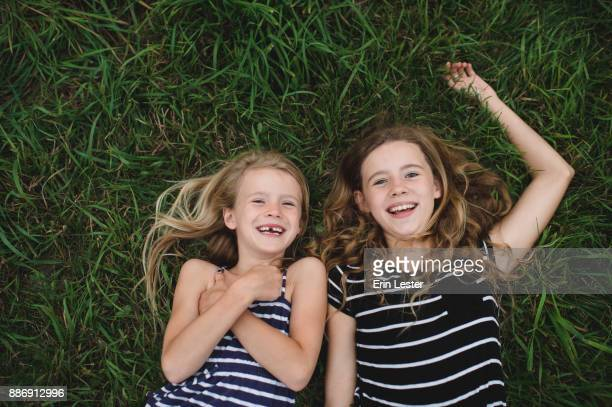 Overhead portrait of girl and her sister lying on grass