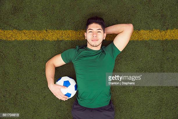 Overhead portrait of young male soccer player lying on football pitch