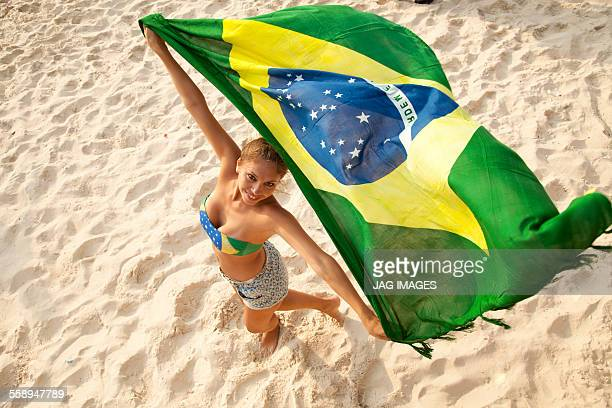 Overhead portrait of young woman holding Brazilian flag whilst dancing, Ipanema beach, Rio De Janeiro, Brazil