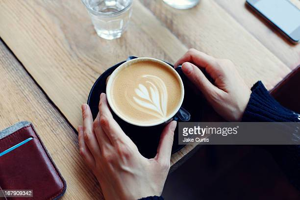overhead shot hands holding cup of coffee at table