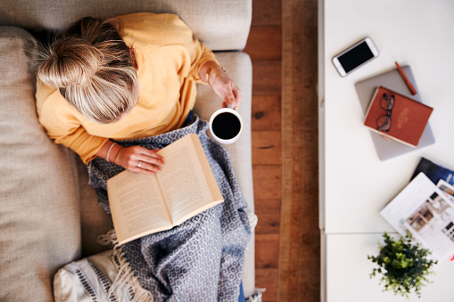 Overhead Shot Looking Down On Woman At Home Lying On Reading Book And Drinking Coffee 1157317608