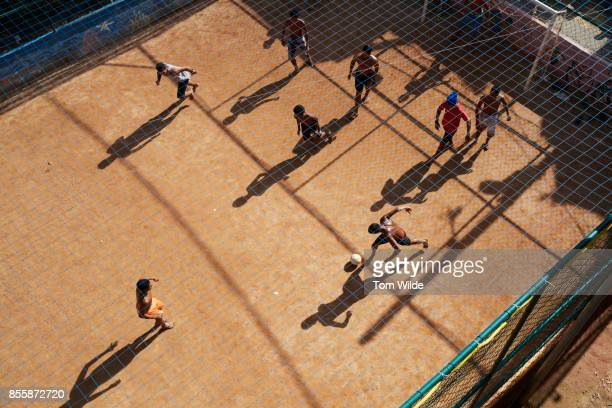 Overhead shot of a group of young men playing football on a dirt court