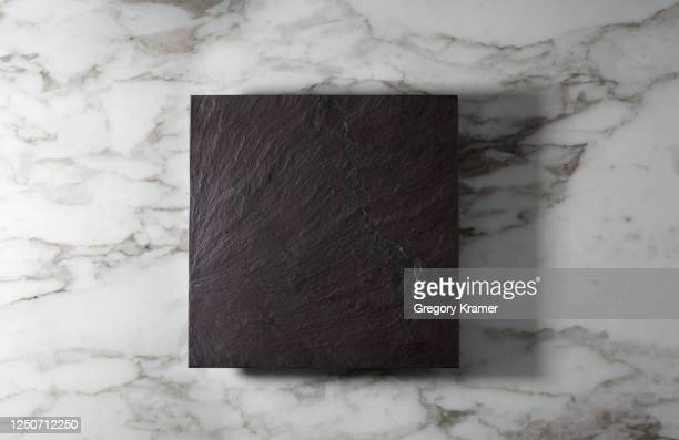 overhead shot of a slate hot plate holder on marble - 台所用品店 ストックフォトと画像