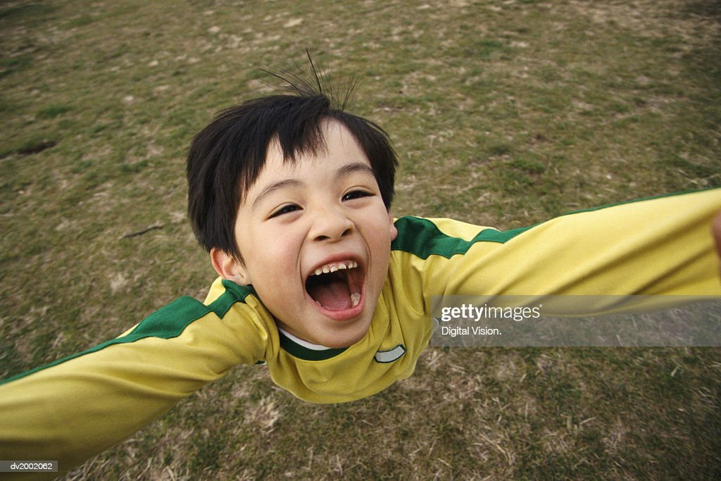 Overhead Shot of a Young Boy with His Arms Raised and His Mouth Open : Stock Photo