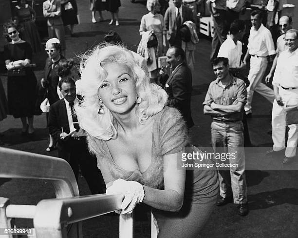 Overhead shot of American actress Jayne Mansfield , leaning on a railing with a crowd of spectators behind her. Undated photograph.
