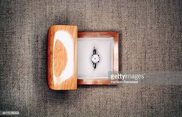 Overhead Shot of an Engagement Ring in a Jewellery Box, on a Fabric Surface