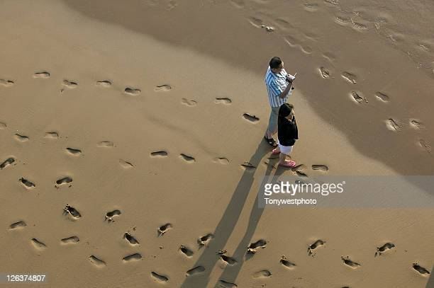 Overhead shot of oriental couple with video camcorder on Blackpool beach