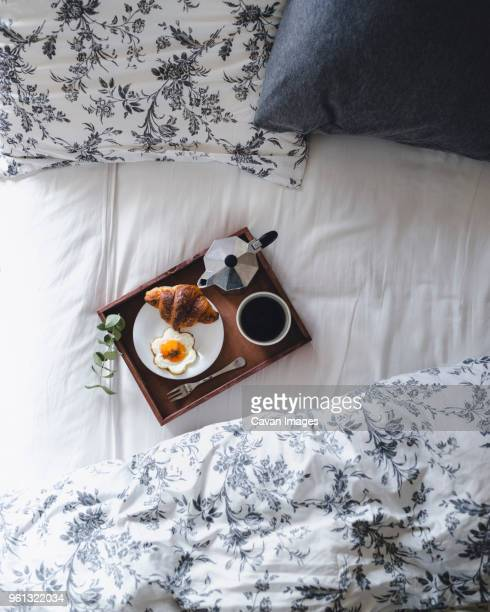 overhead shot of breakfast tray loaded with croissant, fried egg and coffee on bed - breakfast in bed stock pictures, royalty-free photos & images