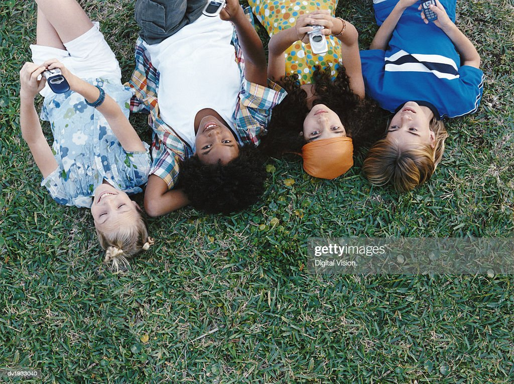 Overhead Shot of Four Young Friends Lying in a Row and Holding Mobile Phones : Stock Photo