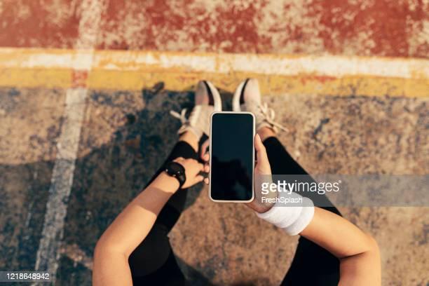 tiro aéreo de mãos de uma esportista segurando um smartphone com uma tela em branco (copy space) - copy space - fotografias e filmes do acervo