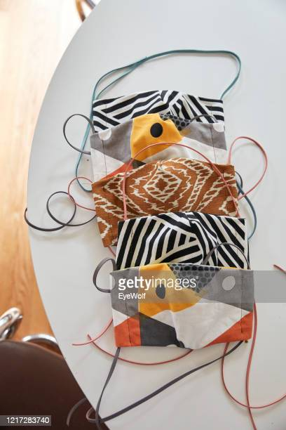 overhead shot of home made face masks sitting on a table - cloth mask stock pictures, royalty-free photos & images