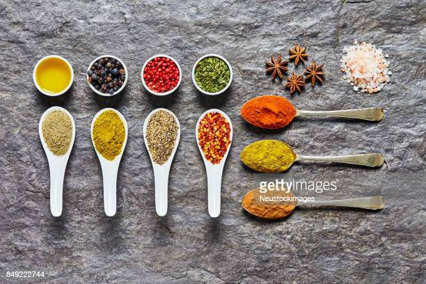 overhead shot of indian curry spices and herbs on slate - garam masala stock photos and pictures