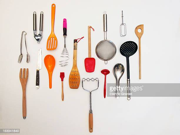 overhead shot of kitchen utensils which appear to be hanging - cooking utensil stock photos and pictures