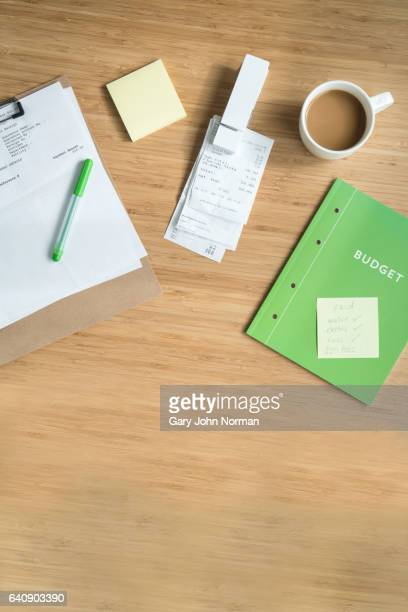 Overhead shot of receipts, bills and budget book on table