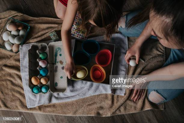 overhead shot of sisters dying chicken eggs - dirty easter stock pictures, royalty-free photos & images
