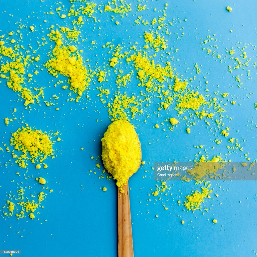 overhead shot of spoon with yellow flour : Stock Photo
