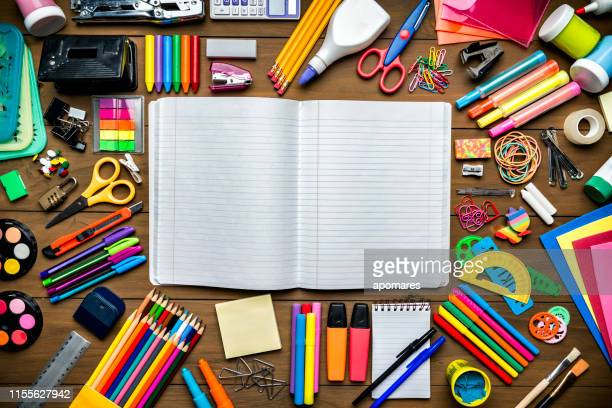 overhead shot of stationery on wood desk with paper notepad and frame of school office supplies - art and craft stock pictures, royalty-free photos & images