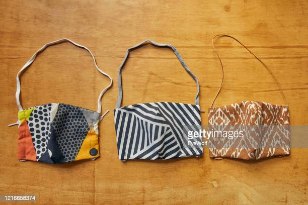 overhead shot of three self-sewn face mask made to protect people from viruses and bacteria, against a wood background. - abstand halten infektionsvermeidung stock-fotos und bilder