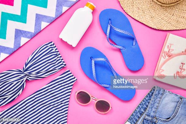 Overhead shot of travel and beach equipment on pink background