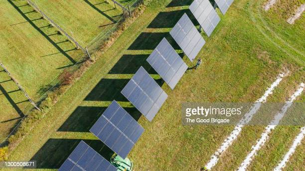 overhead shot of woman walking near solar panels on farm - sustainable lifestyle stock pictures, royalty-free photos & images