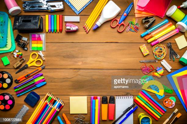 Overhead shot of wood table with frame of school office supplies