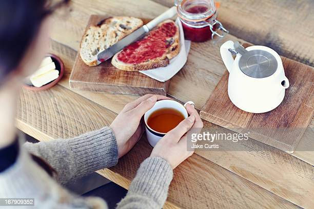overhead shot woman holding cup of tea with bread