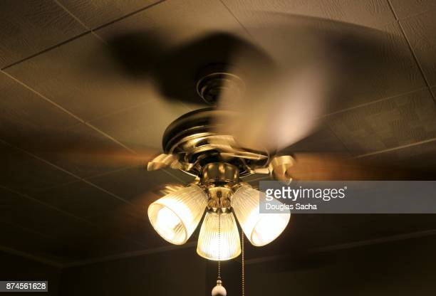 Overhead spinning ceiling fan with illuminated lights