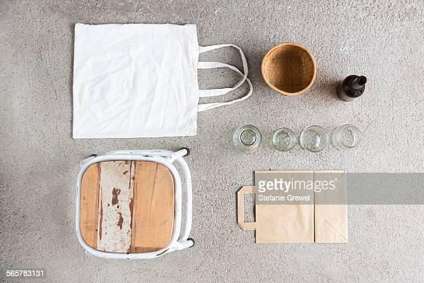 Overhead still life of stool, reusable shopping bag and recyclable paper and bottles