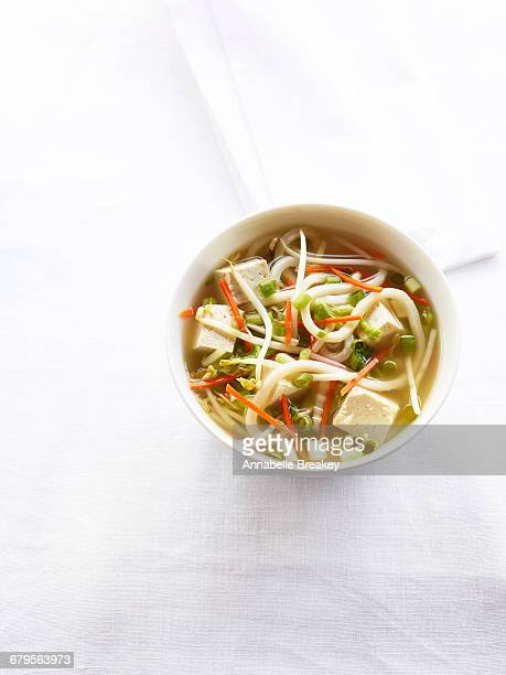 Overhead tofu ginger noodle soup on white