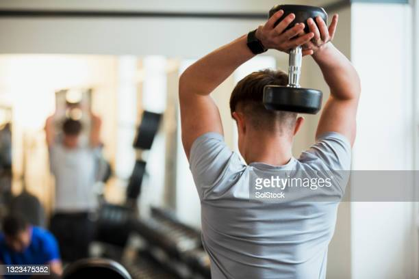 overhead triceps dips with a dumbbell - health club stock pictures, royalty-free photos & images