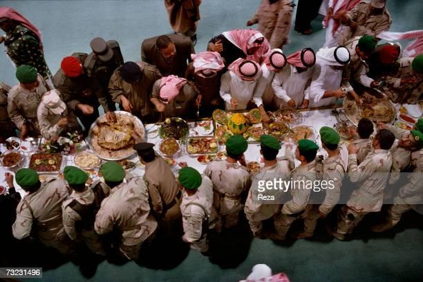 Overhead View as Heir Prince Abdullah bin Abdulaziz Al Saud and Al Saud princes stand at a buffet table during their annual meeting at the Al...