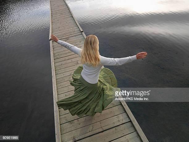 overhead view as woman spins on boardwalk bridge - 回転する ストックフォトと画像