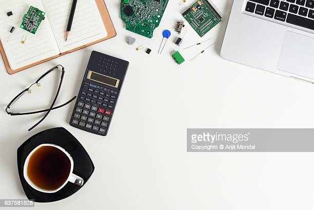 Overhead View Electronic Engineer Assembling Circuit Board with Laptop, Electronic Components, Calculator, Tea